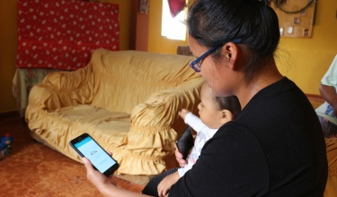 A mother holds her child and looks at an app on her cell phone.