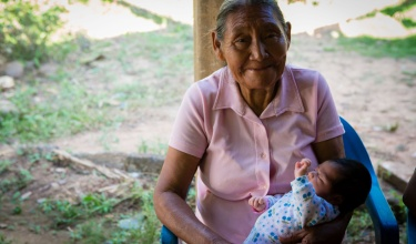 Margarita Perez Jimenez, a traditional midwife, holds an infant she delivered.