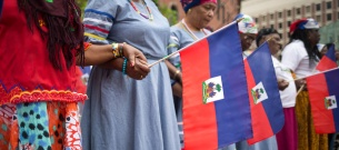 Women hold hands on Haitian Flag Day in Boston