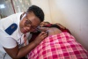 nurse in Lesotho listens to expectant mother's belly for infant's heartbeat